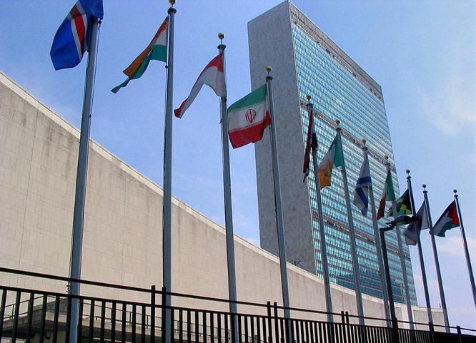 Foto do prédio da sede da ONU em Nova Iorque, com bandeiras de diversos países à frente.