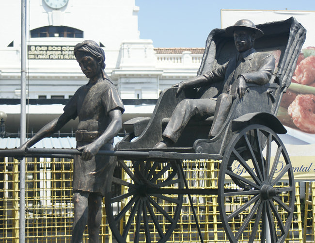 Statue of a colonial planter in a rickshaw